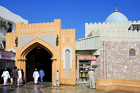 Local residents dressed in traditional clothes at the entrance gate to Souq Muttrah markets, Muscat, Oman, the Near East