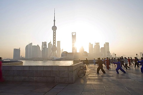 Chinese people practicing Tai Chi at the Bund, in front of the Pudong Skyline, Shanghai, China, Asia