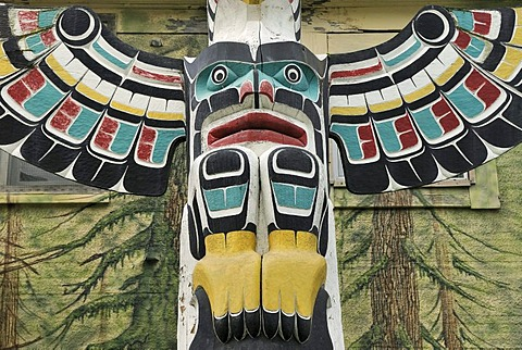 Totem pole of the Cowichan Indians, close-up, in front of a painted house wall, Duncan, Vancouver Island, Canada, North America