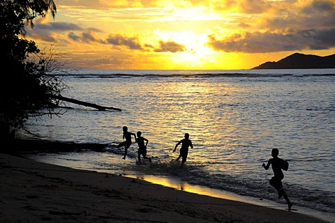 Children playing by the sea at sunset, Anse La Reunion, La Digue, Seychelles