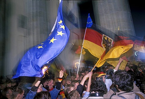 German flags, citizens of Berlin celebrating the reunion of East and West Germany in front of the Brandenburger Tor at night, DDR, October 3rd 1990, Berlin, Germany, Europe