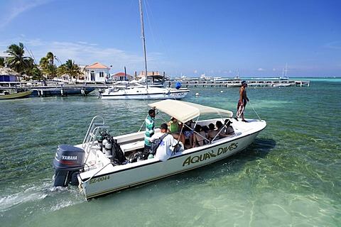 Diving boat loaded with scuba divers heads out to sea, San Pedro, Ambergris Cay Island, Belize, Central America, Caribbean