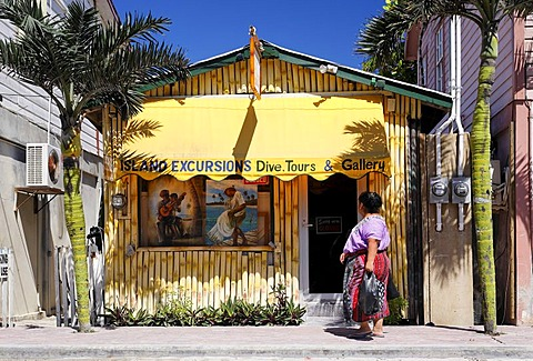 Shop made of bamboo between two palm trees, pedestrian woman, in San Pedro, Ambergris Cay Island, Belize, Central America, Caribbean