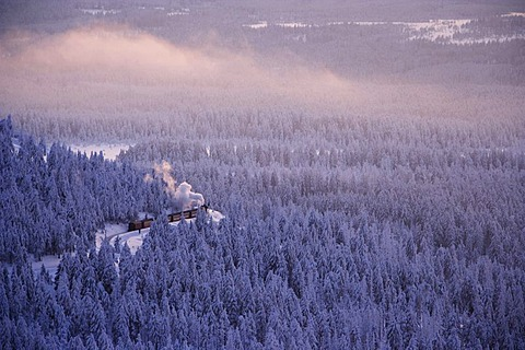 View from the Brocken mountain over a winter landscape deeply covered in snow at sunset and the Harzer Schmalspurbahn, narrow-gauge railway with steam engine, Saxony-Anhalt, Germany - 832-266564