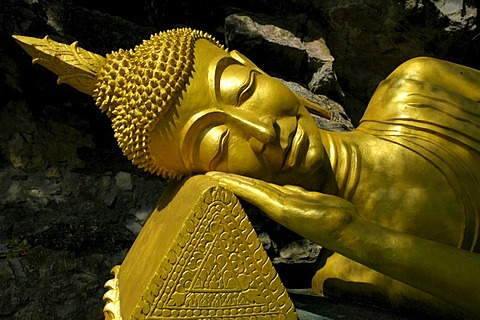 Lying head of the reclining Buddha in the Wat Tham Temple, on Phu Si Mountain, Luang Prabang, Laos, Southeast Asia