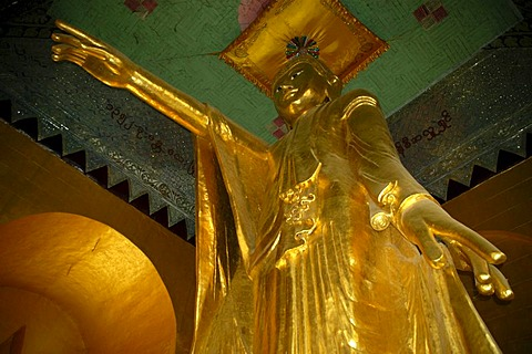 Large standing golden Buddha statue with outstreched arm and pointing finger, shrine on Mandalay Hill, Birma, Burma, Myanmar, South Asia