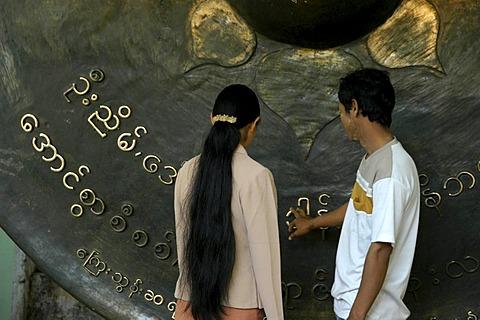Couple wishing for future luck, touching large brass gong, Burmese scripture, Mandalay, Birma, Burma, Myanmar, South Asia