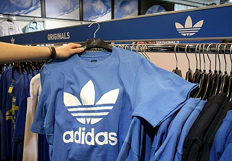An employee holding a t-shirt with an Adidas logo in an outlet store of the Adidas Salomon AG in Herzogenaurach, Bavaria, Germany, Europe