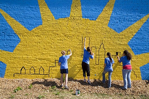 Volunteers in the Summer in the City program, a community improvement project, painting a mural on a building, Detroit, Michigan, USA