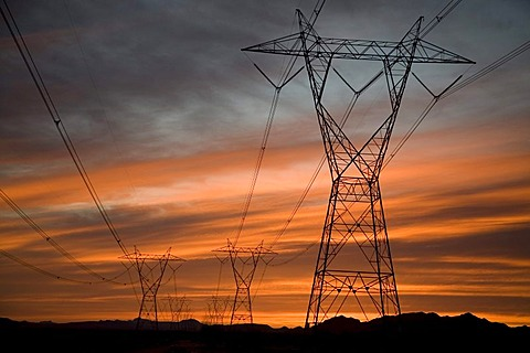 An electrical power line is silhouetted against the sunset in the Sonoran Desert, Palo Verde, Arizona, USA