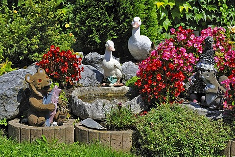 Garden gnomes and figurines of ducks, squirrels and a bear in a Bavarian garden near Munich, Germany, Europe