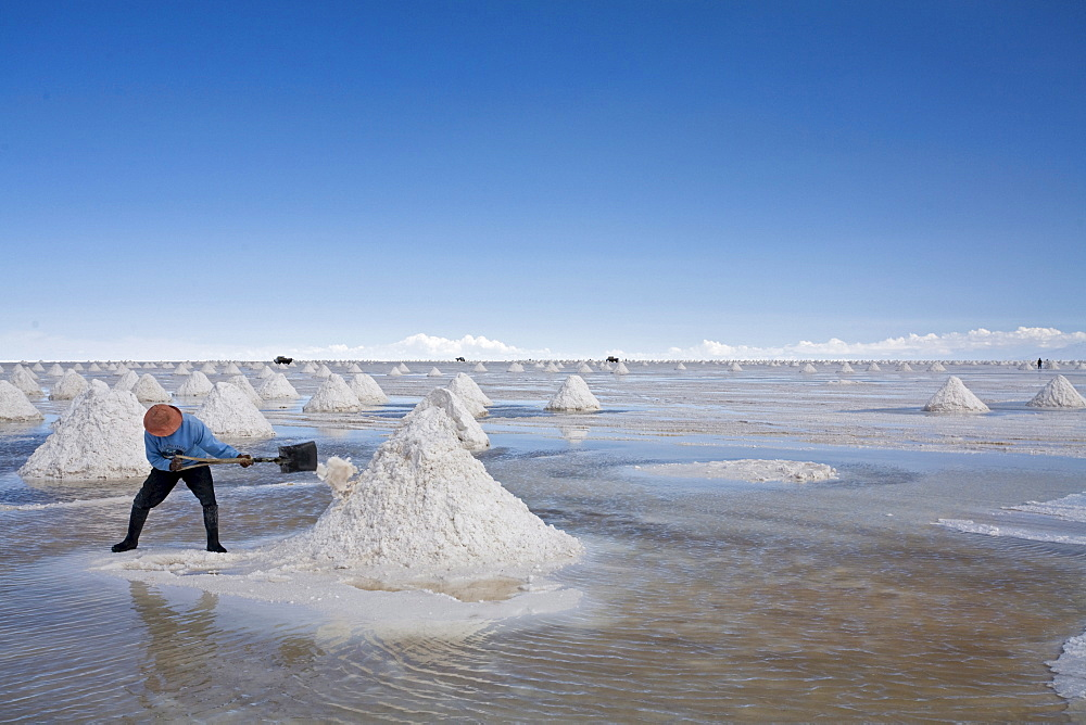 Salt worker makes salt accumulation, salt lake Salar de Uyuni, Altiplano, Bolivia, South America