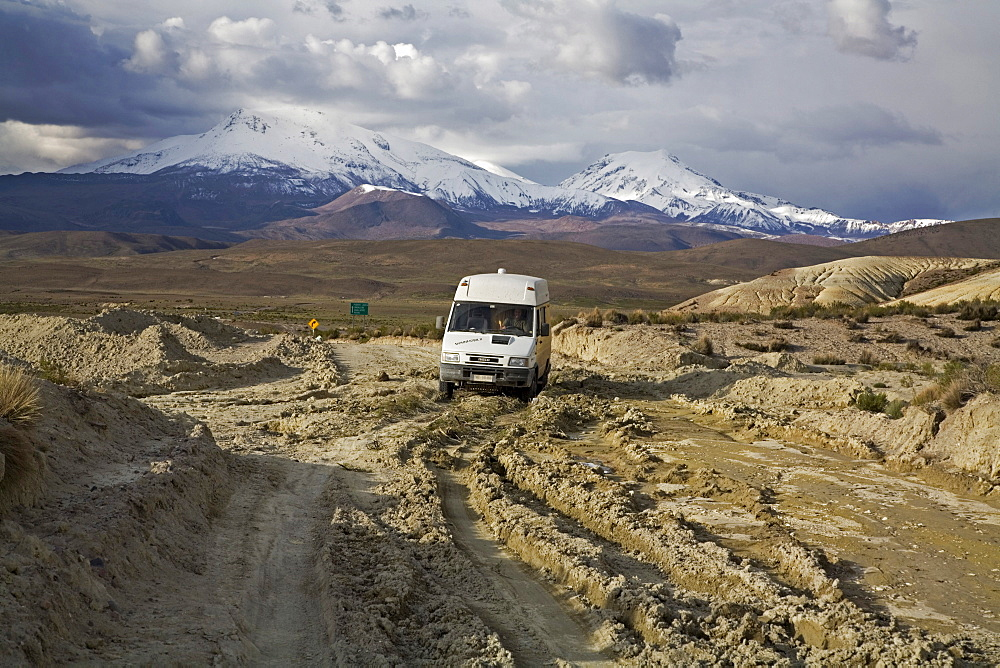 Camper on a destructed road from the rain in national park Lauca on the way to national park Reserva Nacional Las Vicunas, Chile, South America