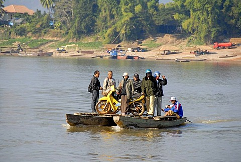 Adventurous ferry with people and a motobike across the Mekong River Champasak Laos