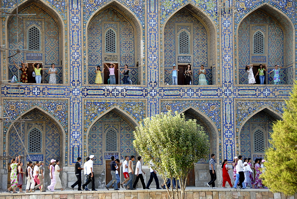 Young women dancing in arches of Madrasah Tilla-kari Registan Samarkand Uzbekistan