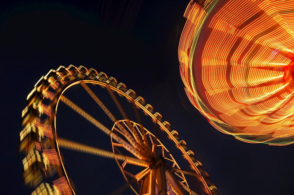Ferris wheel and swing carousel (chair-o-plane) at a fair in Stuttgart, Baden-Wuerttemberg, Germany, Europe