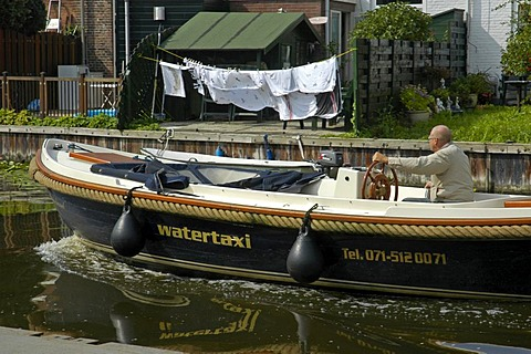 Water cap with driver in a canal, with hung up clothes in the background, Leiden, South Holland, Holland, The Netherlands