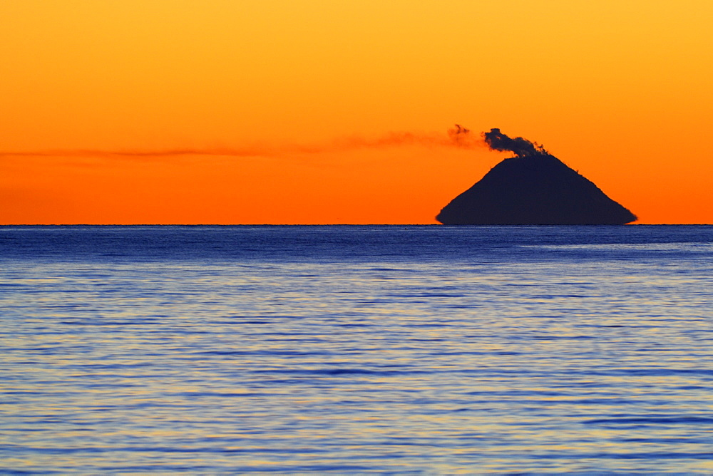Smoke coming from Mt. Augustine Volcano (Ring of Fire) at sunset, picture taken from ca 140 km away, Kenai Peninsula, Alaska, USA