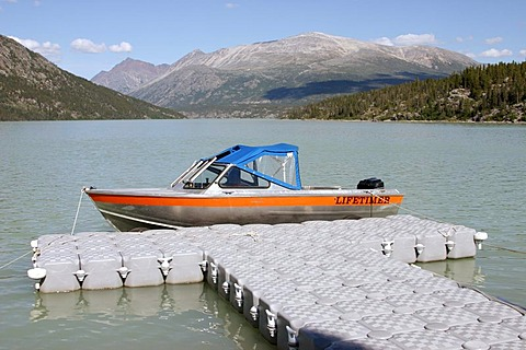 Footbridge made aot of plastik pontoons and the motor boat of the ranger at the Lake Lindemann Chilkoot Trail British Columbia Canada