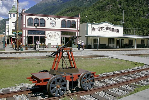 A handcar in front of historical wooden buildings in the gold rush town of Skagway Alaska USA