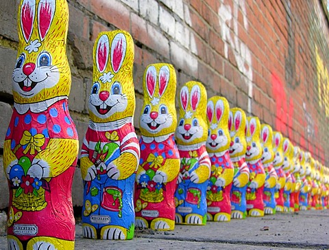 A group of over twenty easter bunnies from chocolate in a row in front of a wall with graffiti - 832-285337