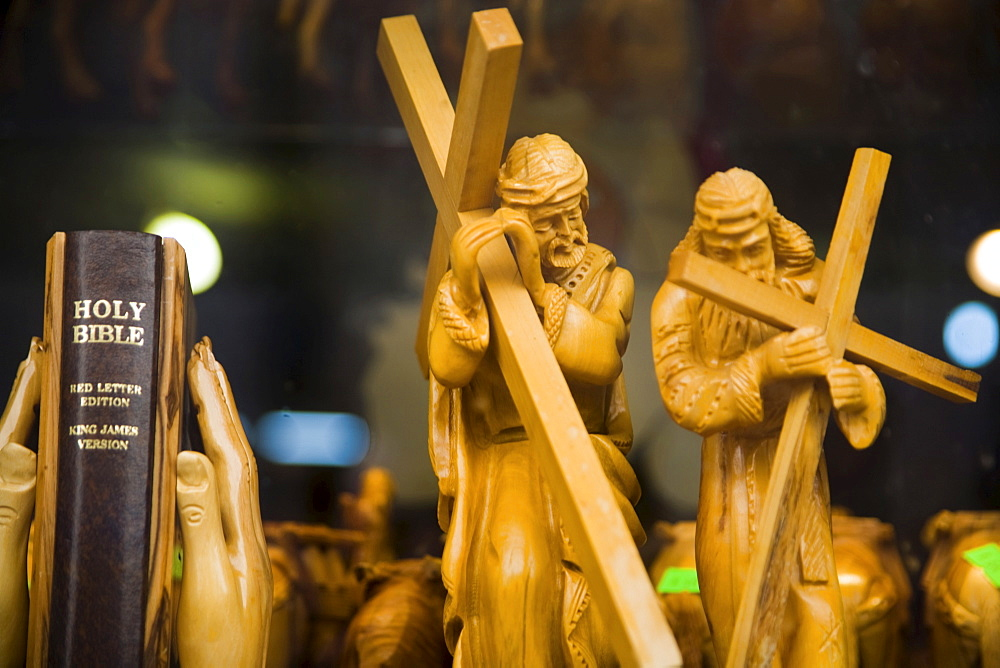 Two carved wooden figures of Jesus carrying the cross and praying hands as bookends, bible, Bethlehem, West Bank, Palestine, Israel, Middle East