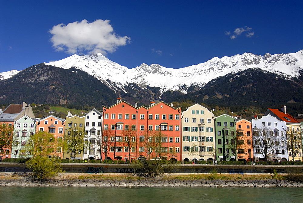 Row of buildings on Mariahilf Street along the Inn River, snow covered Karwendel Mountain Range of the Alps at back, Historic centre of Innsbruck, Inntal Valley, Tyrol, Austria, Europe