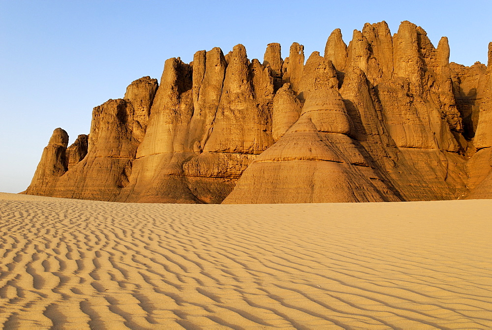 Eroded rock formations rising out of desert sand dunes, ripples in Tin Akachaker, Tassili du Hoggar, Wilaya Tamanrasset, Sahara Desert, Algeria, North Africa