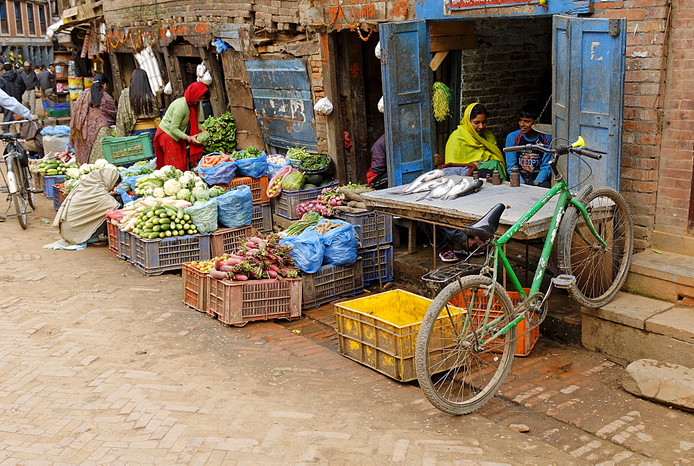 Locals buying and selling fish and vegetables in the market in the old town of Bhaktapur, UNESCO World Heritage Site, Kathmandu, Nepal, Asia