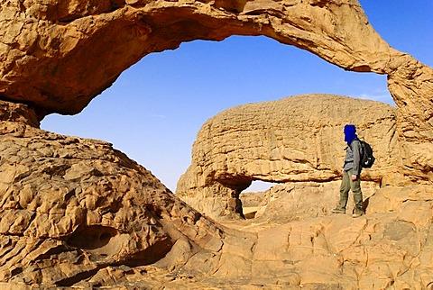 Man standing underneath the rock arch of Youf Ahakit, Tassili du Hoggar, Wilaya Tamanrasset, Algeria, Sahara Desert, North Africa, Africa