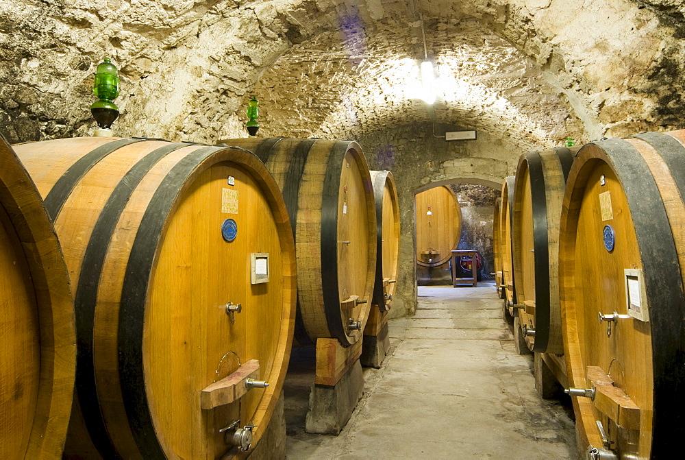 Wine barrels in a wine cellar, Castellina in Chianti Fattoria, Chianti Region, Tuscany, Italy