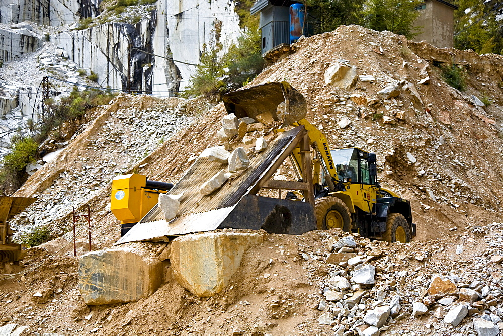 Mechanical shovel excavator at work in the marble stone pit of Carrara Tuscany Italy