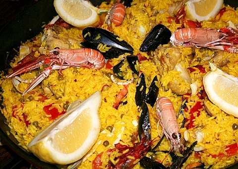 Spanish traditional food a pan of Paella with rice and seafood shrimps, mussels, spiny lobster and lemon