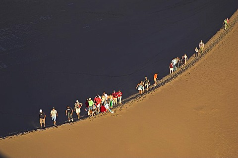 People on a sand dune in the Moon Valley (Valle de la luna), Atacama desert, northern Chile, South America