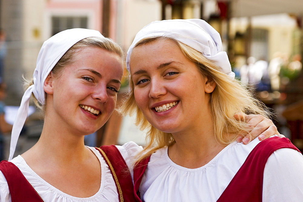 Young women dressed in traditional clothing standing in front of Olde Hansa restaurant, Tallinn, Estonia, Europe