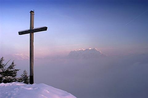 Pendling, cross of the peak, in front of Kaisergebirge in winter, Tyrol, Austria