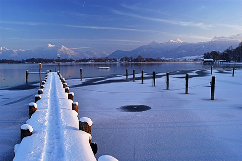 Snowy landing stage and lantern in front of Hochgern, Lake Chiemsee, Bavaria, Germany