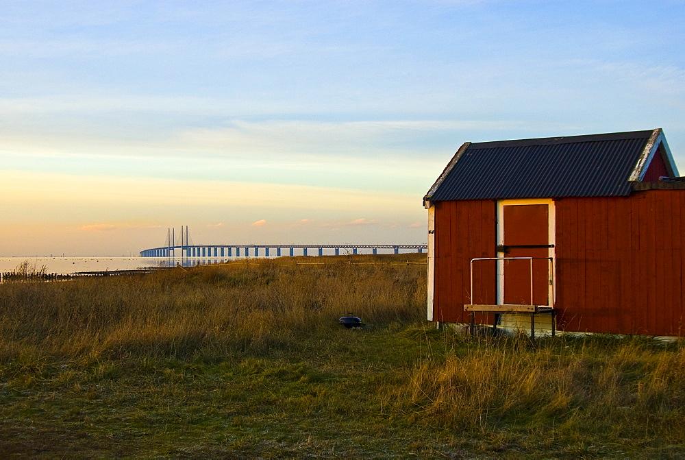 Oeresund Bridge and a red wooden house among the reeds, Skania, Schonen, Sweden, Scandinavia, Europe