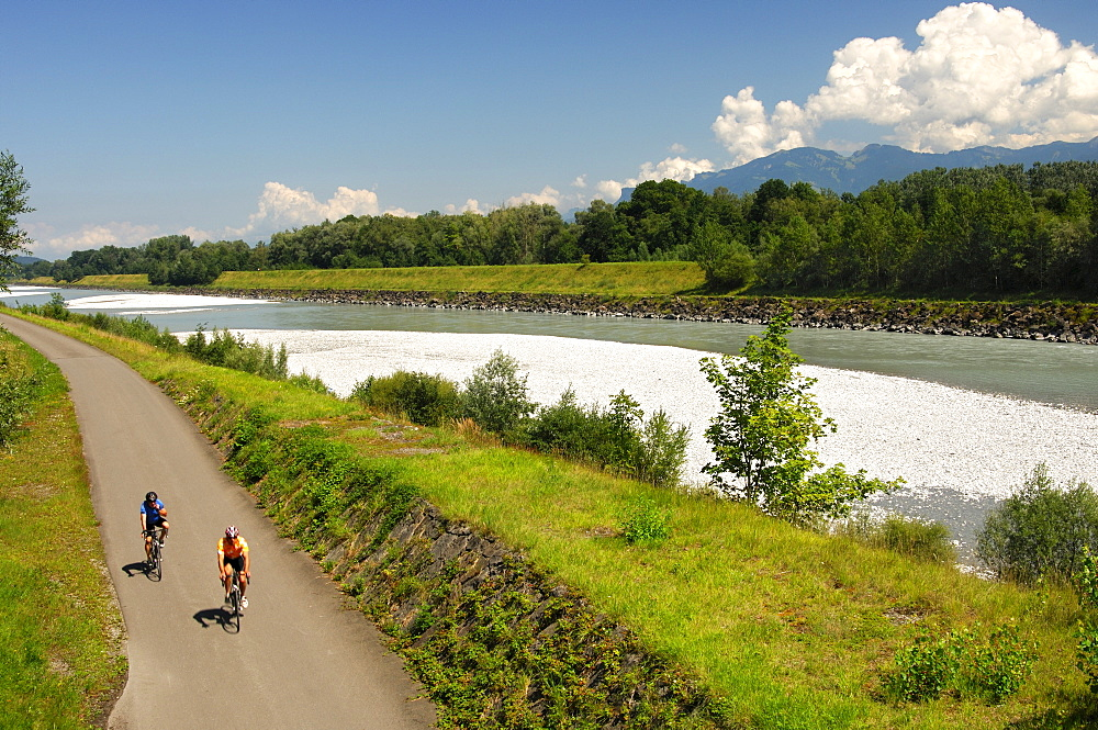 Cyclists in the Rhine River Valley, view from the left bank (Swiss side) toward Liechtenstein on the right bank
