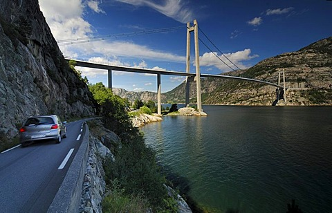 Car driving on a street along the Lysefjord with suspension bridge, Forsand, Rogaland, Norway