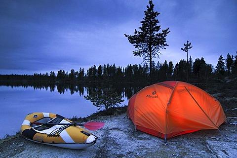 Illuminated tent and canoe at dawn, Femund, Femundsmarka national park, Norway