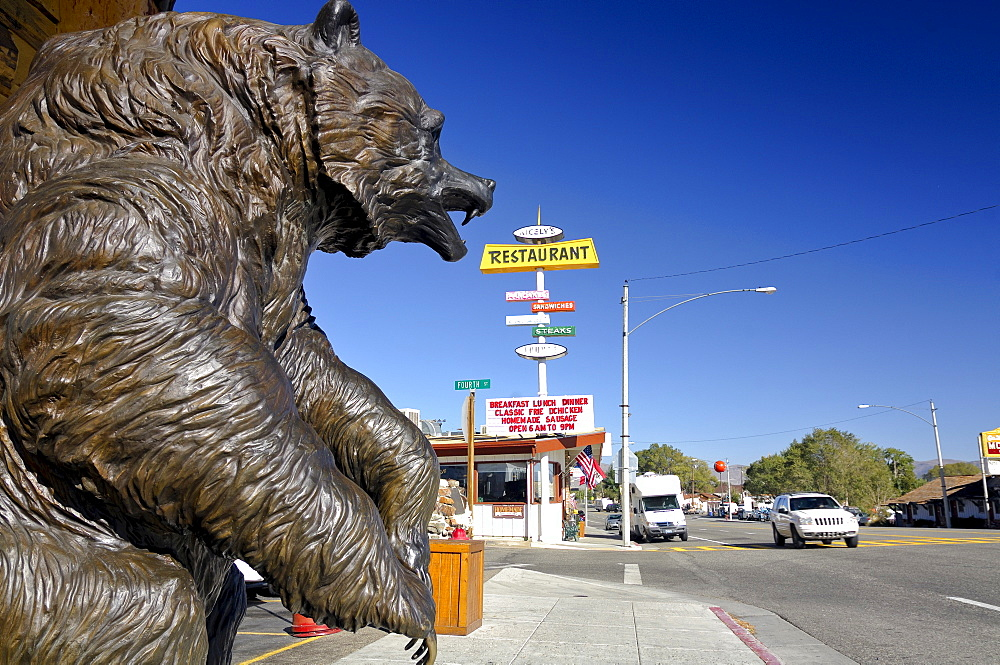 Statue of a brown bear and various billboards lining the main street in Lee Vining near Mono Lake, California, USA, North America