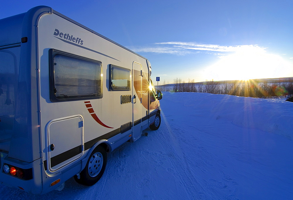 Camper driving through wintry landscape at sunset, Finnmark, Norway, Scandinavia