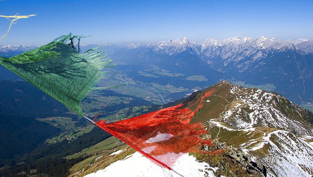 View over Inn Valley toward the Karwendel Range, prayer flags flapping in the wind, Kellerjoch Cabin, Schwaz, Tirol, Austria