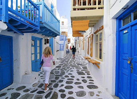 Blonde woman walking through an alleyway sided with blue wooden doors, Mykonos Island, Cyclades, Greece, Europe