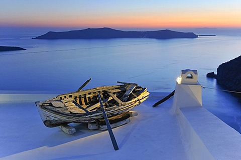 Old rowboat displayed on a rooftop terrace at sunset in front of the blue sea and the volcanic island of Nea Kameni, Thira, Fira, Santorini, Cyclades, Greece, Europe - 832-303393