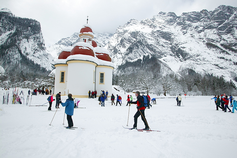 St. Bartholomew's Church at the frozen Koenigssee, cross-country skiers, Berchtesgadener Land, Upper Bavaria, Germany