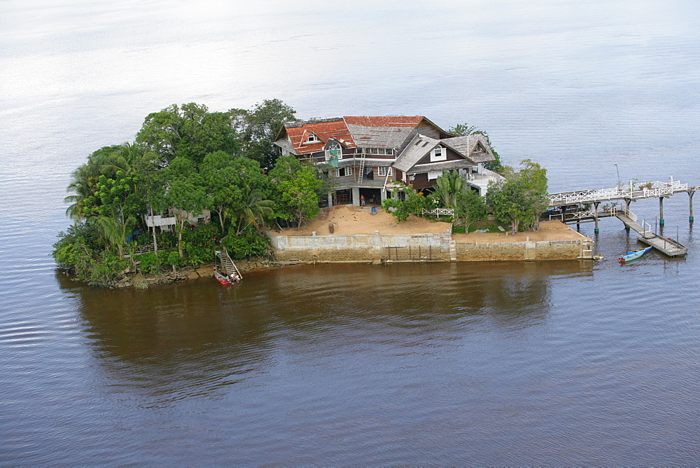 Aerial view of a house built on an island in Demerara River, Guyana, South America
