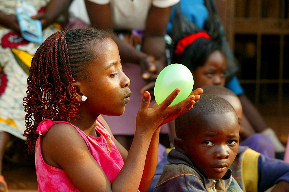 Girl holding balloon, Cameroon, Africa