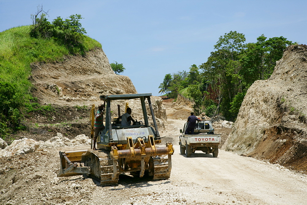 Earth mover building a road for the refinery and harbour area of the Ramu Nickel Mine, chinese mining company, Basamuk, Papua New Guinea, Melanesia